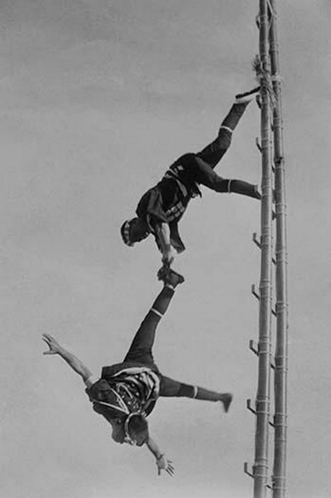 Two Tokyo Firefighters display acrobatic skill on very high bamboo ladders - Art Print