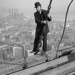 Cameraman in suit holds onto cable as he walks unharnessed over a skyscraper's steel girders - Art Print