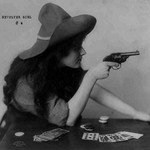 Young Cowgirl Hold Pistol Over a table of Playing Cards - Art Print