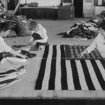 Flags laid out on cutting table to be sewn by Seamstresses who will make American ensigns during the period of the Great War - Art Print