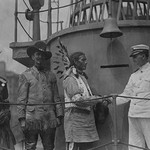 A War Bonneted Native American shakes hands with the Commander of the 'Recruit', a facsimile Battleship constructed in the center of Manhattan to aid in enlisting men to fight in Europe in WWI; - Art Print