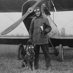 Aviator and His dog wear goggles in front of his Biplane - Art Print