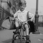Toddler on Tricycle Carries small satchels after making a food sale - Art Print