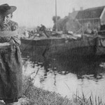 A Older Dutch woman has a bustle around her chest as she pulls a barge down a canal. - Art Print