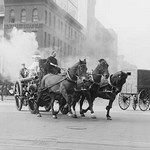 A Team of Horses pulls a steam pumper across paved streets toward a fire scene. - Art Print