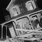 Men stand on Porch of a Sea bright Cottage torn from its foundation and tilted at a 45 degree angle. - Art Print