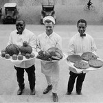 Three Chefs stand on bottom of a line of steps and hold up Thanksgiving platters of Pies, apples and a Turkey - Art Print