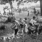 Group of Boys carry loaves of bread from wagons near beach front in woods. - Art Print
