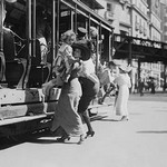 Woman lifts child off of an open sided Trolley Car on New York's Broadway - Art Print