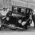 Automobile apparently hit the curb and cracked its front axle following which are attracted a group of onlookers - Art Print