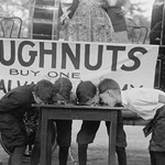 Boys Chow Down on a Table in a Donut Eating Contest - Art Print