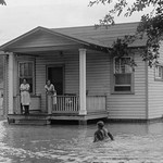 Children on porch of house surrounded by flood - Art Print