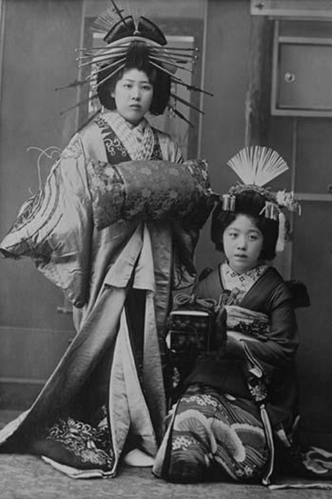 Two Young Beautiful Japanese Geishas accoutered in the ceremonial costumes and hairstyles of ancient Japan with Kimono, Combs and Obi - Art Print