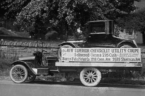 Truck carries a Chevrolet Coupe Advertisement with an actual vehicle on board - Art Print